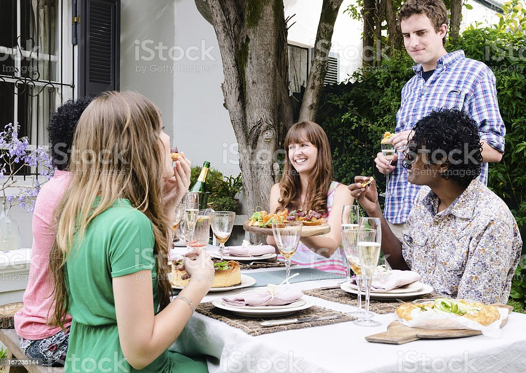 Friends enjoying food and drinks at a social party gathering royalty-free stock photo