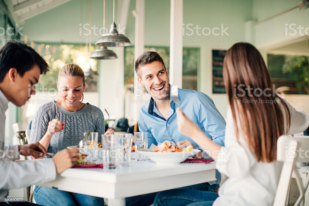 Friends Enjoying Lunch In Restaurant. stock photo