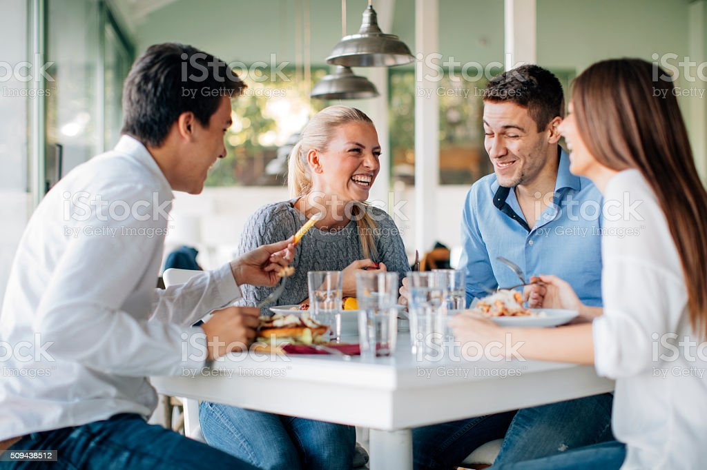 Friends Enjoying Lunch In Restaurant stock photo