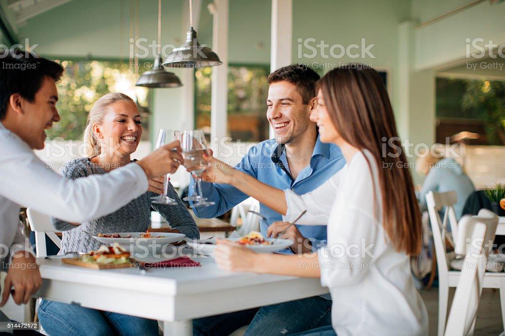 Friends Enjoying Lunch In Restaurant. stock photo