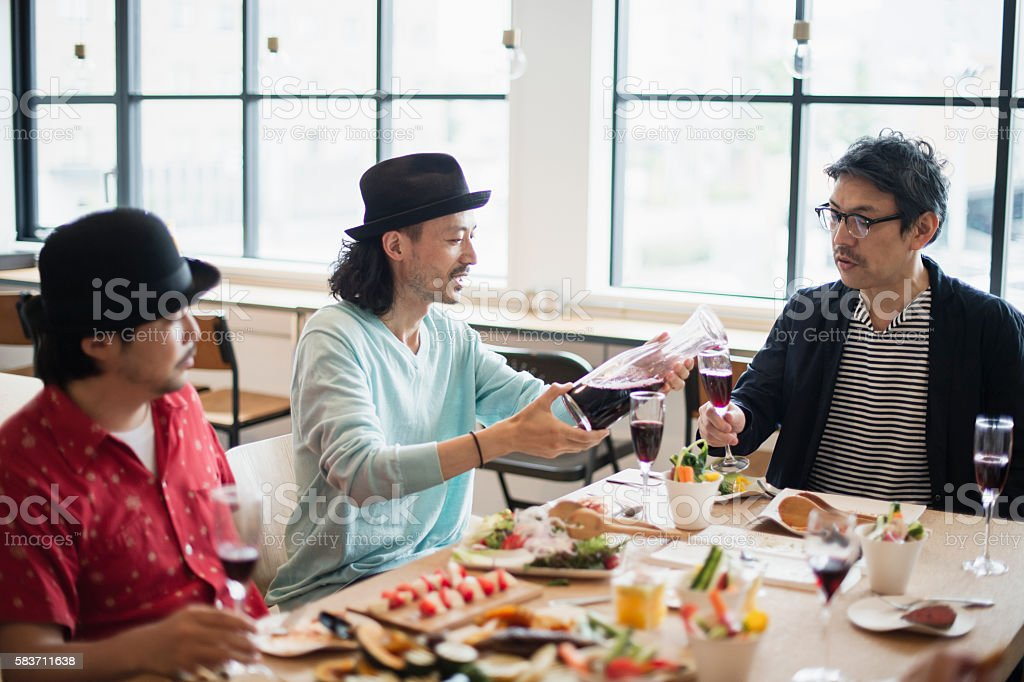 Friends enjoying lunch party at a guesthouse stock photo