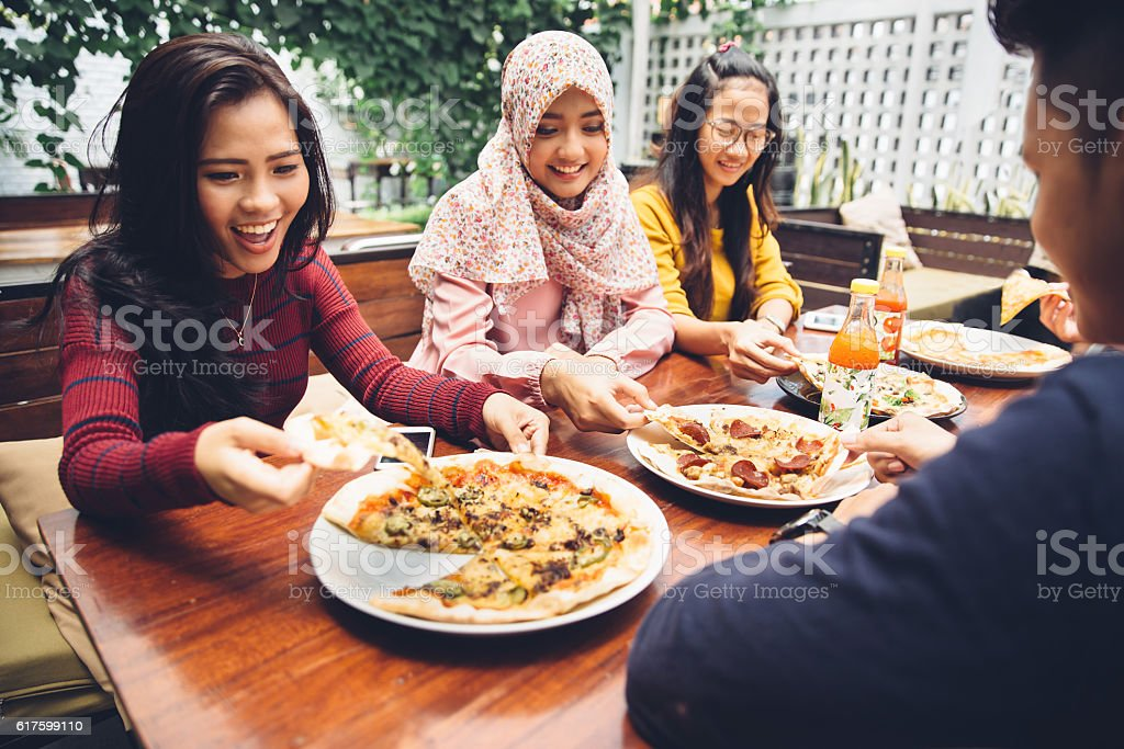 Friends Enjoying Meal In Outdoor Restaurant stock photo