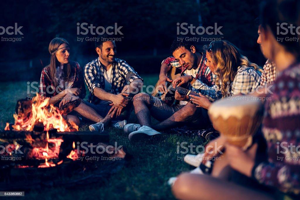 Friends enjoying music near campfire stock photo