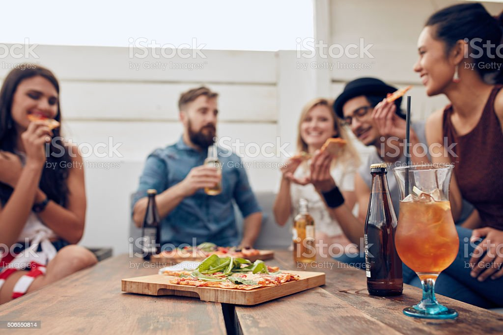 Friends enjoying pizza and drinks in party stock photo