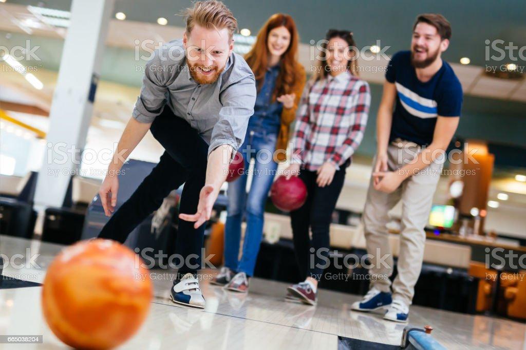 Friends enjoying recreational  bowling at club stock photo