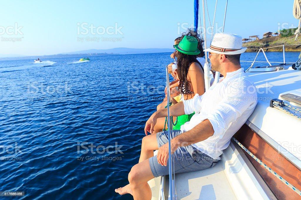 Friends enjoying sailboat ride stock photo
