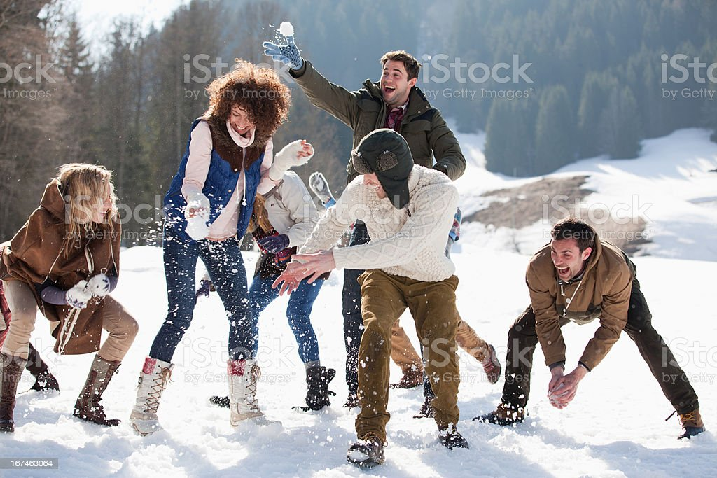 Friends enjoying snowball fight in field royalty-free stock photo