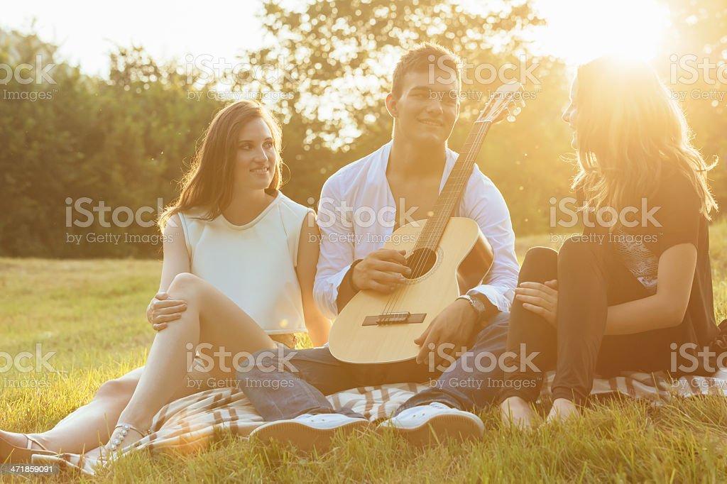 Friends Enjoying Summer Sunset Outdoors royalty-free stock photo