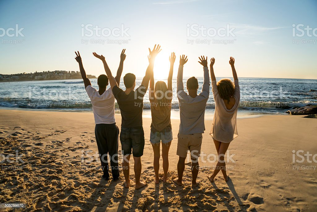 Friends enjoying the sunset at the beach stock photo