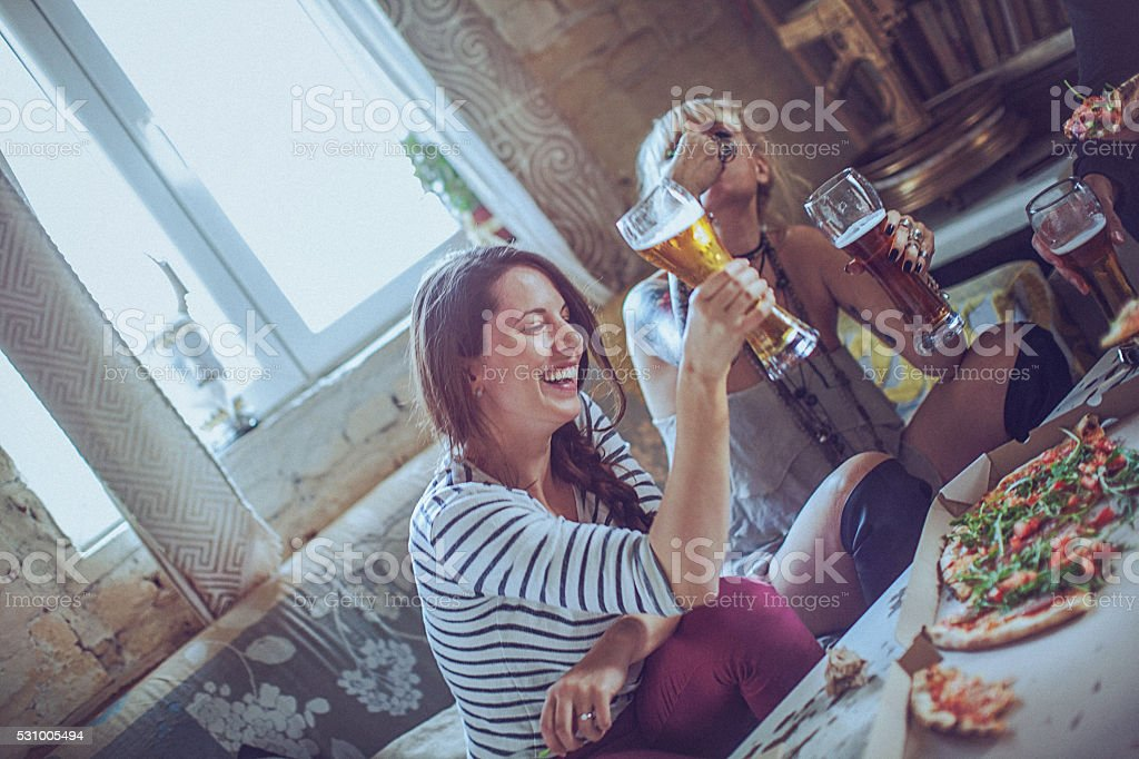 Friends enjoying time eating pizza and drinking beer together stock photo