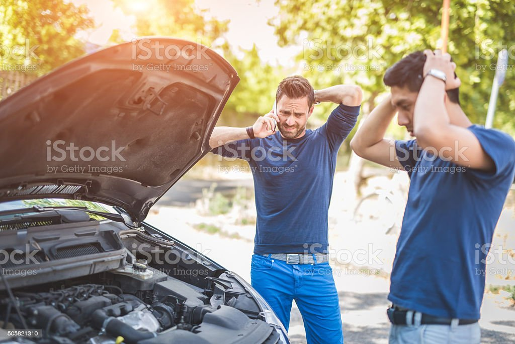 Friends examining broken down car on sunny day stock photo