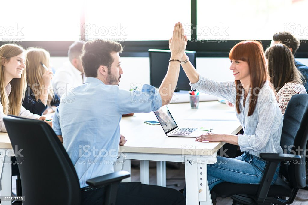 friends exchanging the highfive in the office stock photo