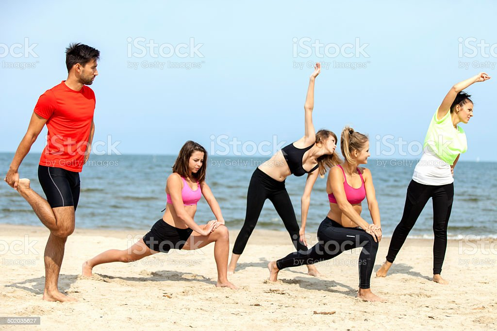Friends Exercising On Beach royalty-free stock photo