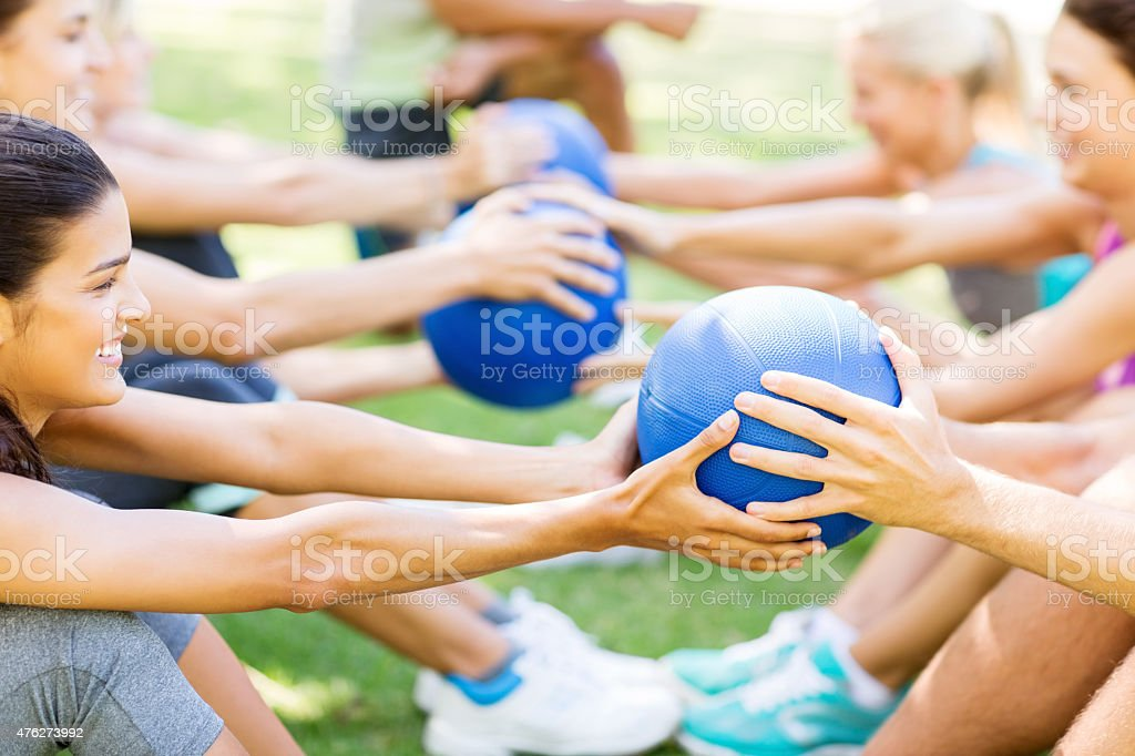 Friends Exercising With Medicine Balls In Park stock photo
