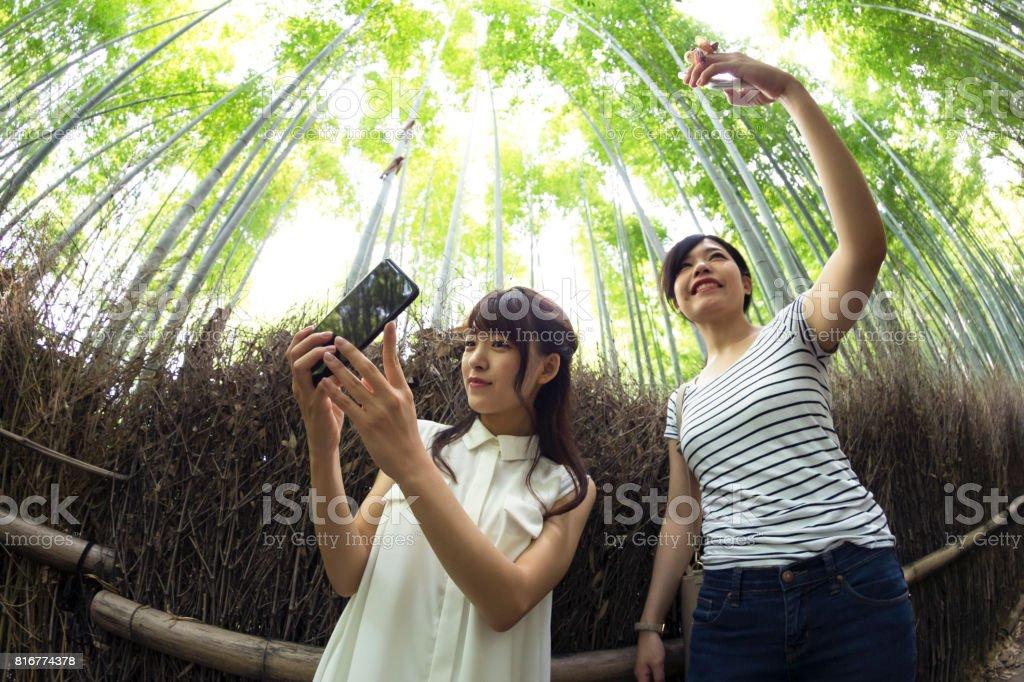 Friends exploring Arashiyama, Kyoto and taking selfie for social media stock photo