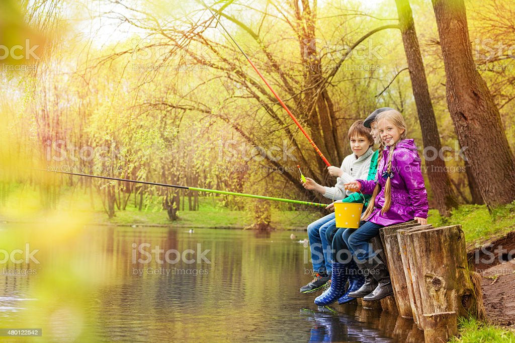 Friends fishing together with colorful fishrods stock photo
