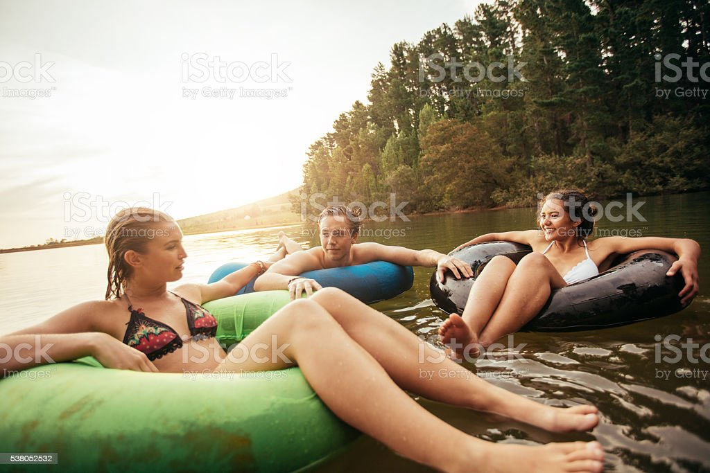 Friends floating on lake with inflatable rings stock photo