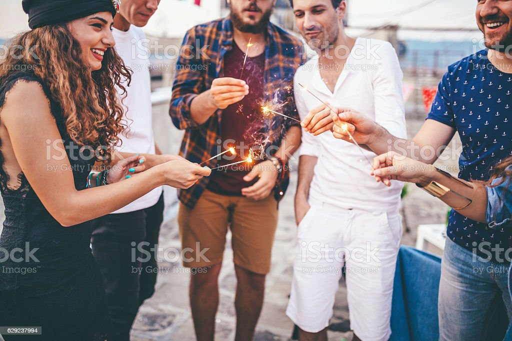 Friends folding sparklers on rooftop terrasse at sunset stock photo
