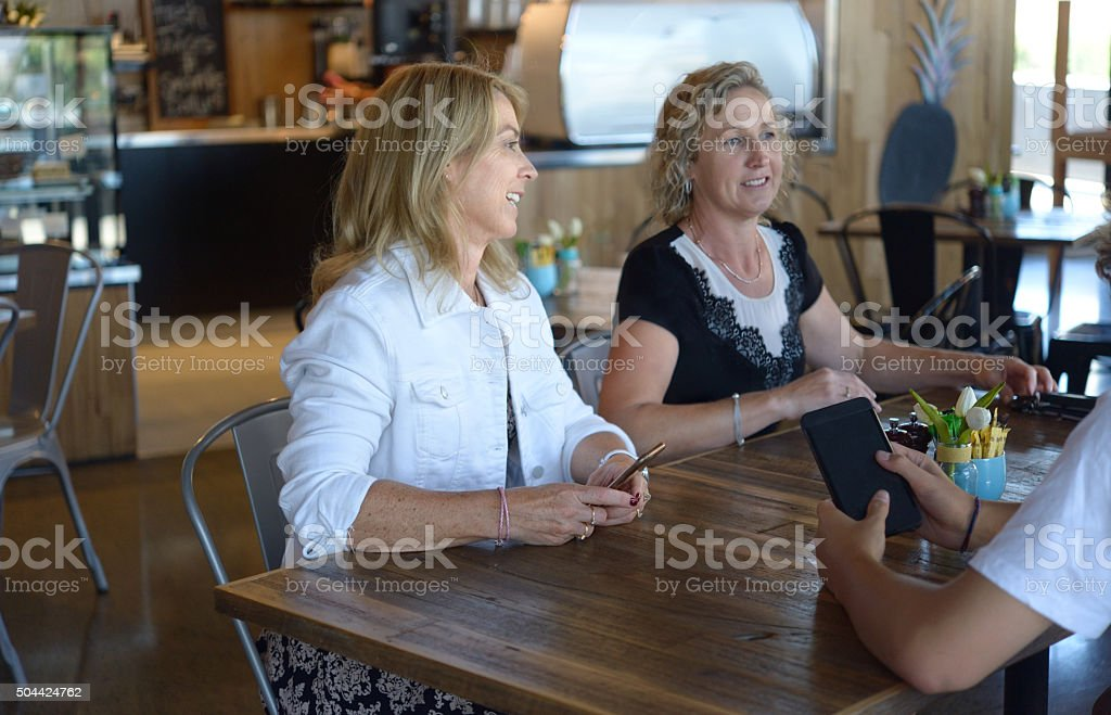 Friends for Coffee holding Cell Phones stock photo