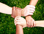 Friends forever! Four hands clasped in square against grassy background