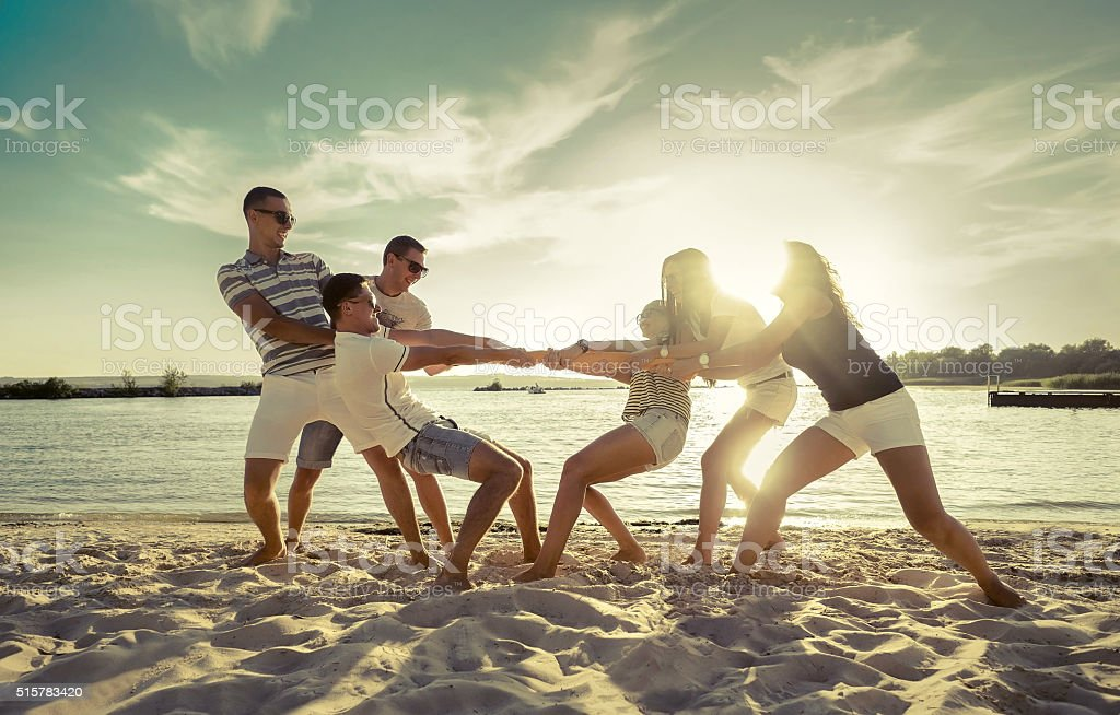 Friends funny tug of war on the beach under sunset stock photo