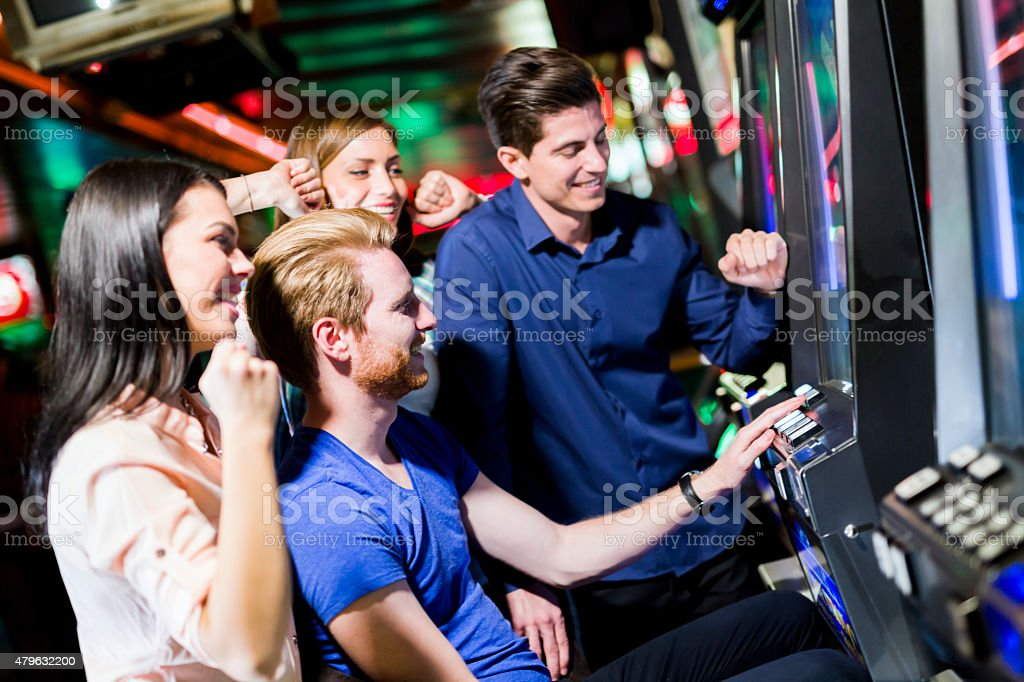 Friends gambling in a casino playing slot and various machines stock photo