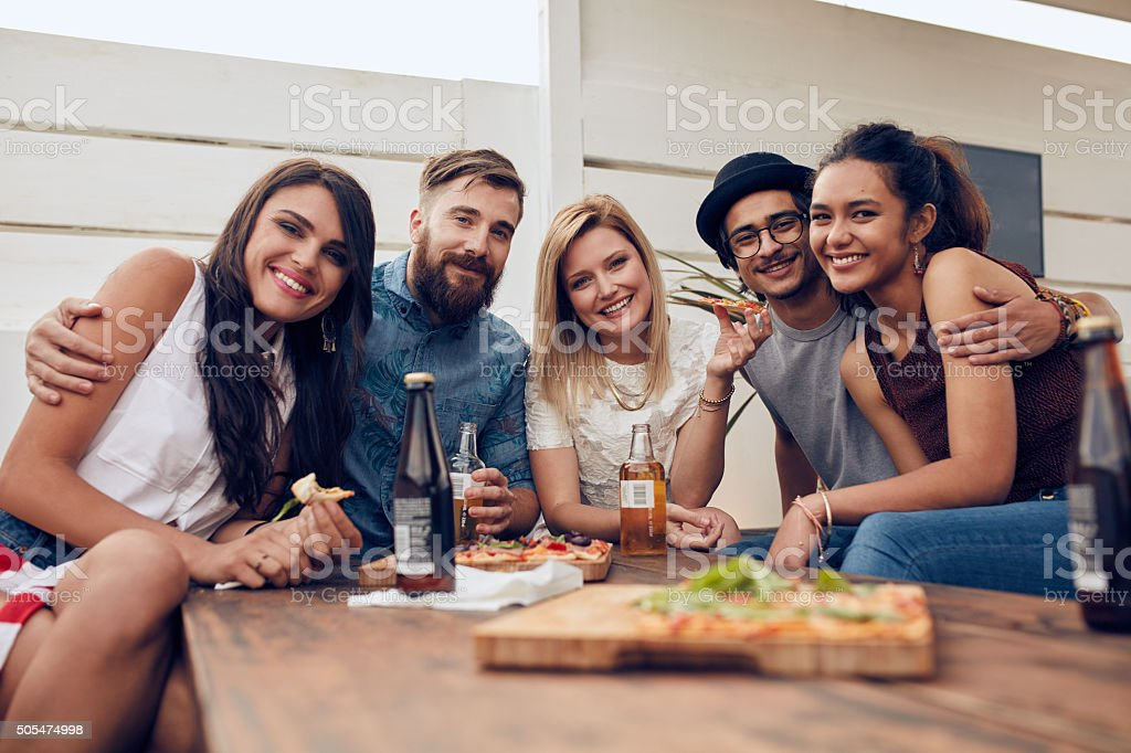 Friends gathered around the table at a roof party stock photo