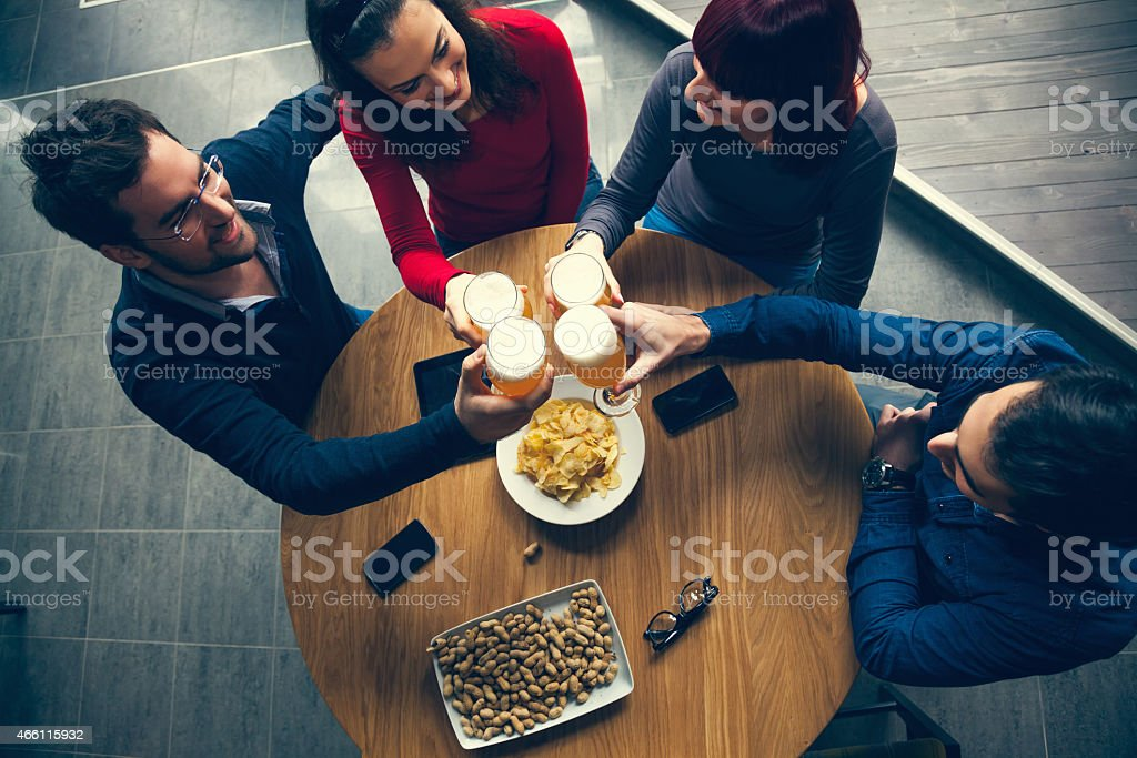 Friends gathered in a bar to have drinks and food stock photo