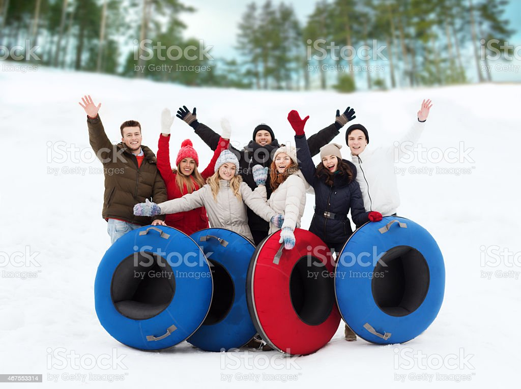 Friends gathered together with snow tubes stock photo