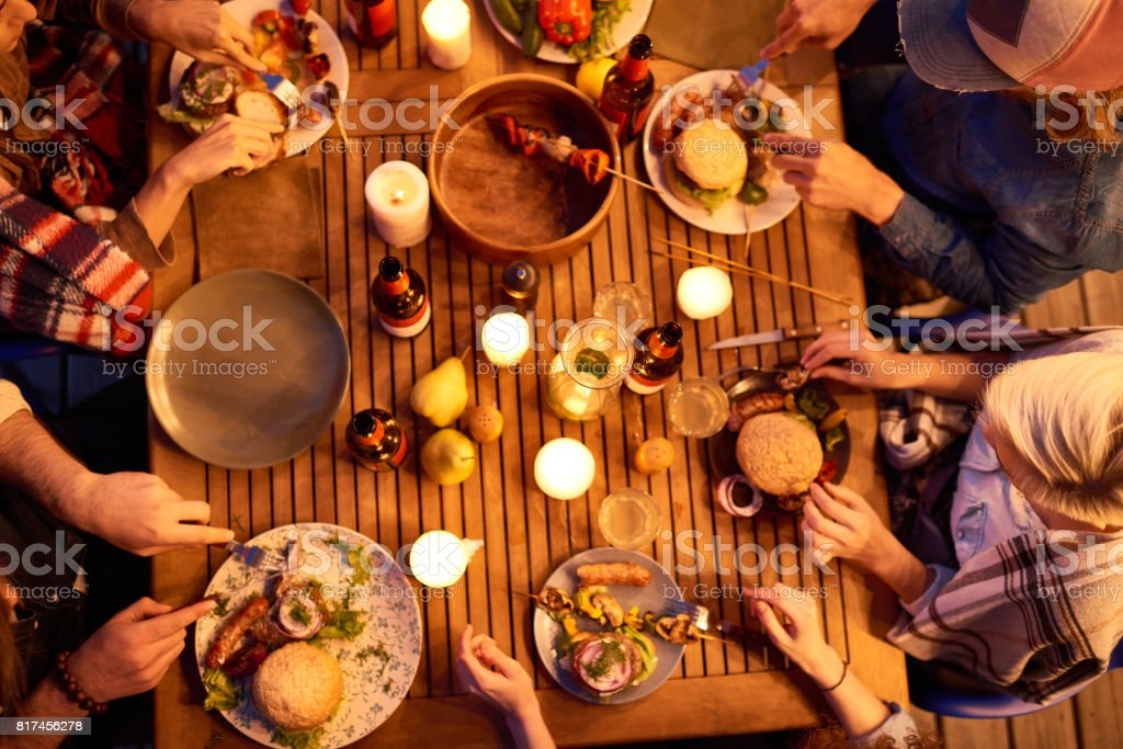 High angle view of close friends enjoying outdoor dinner party by...