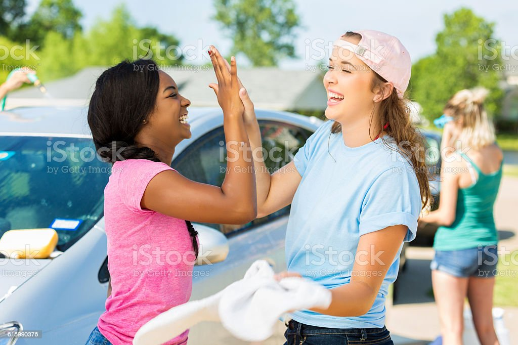Friends give high fives while washing cars at fundraising event stock photo