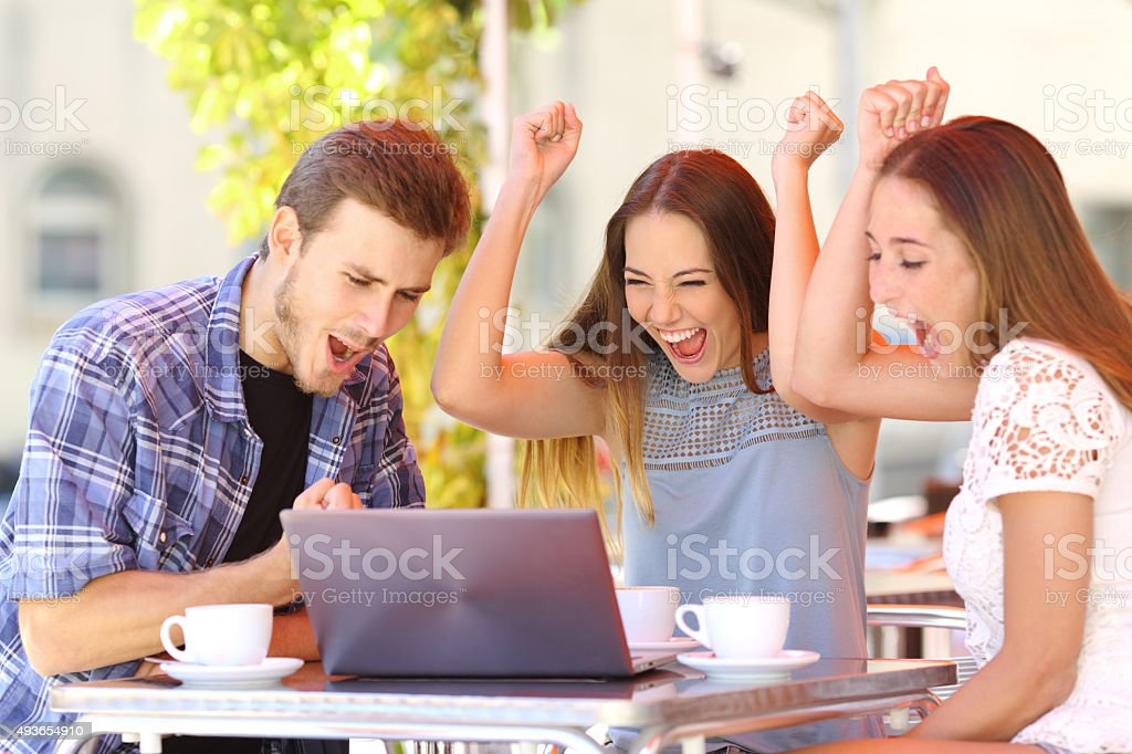 Friends giving a laptop gift to a surprised girl stock photo