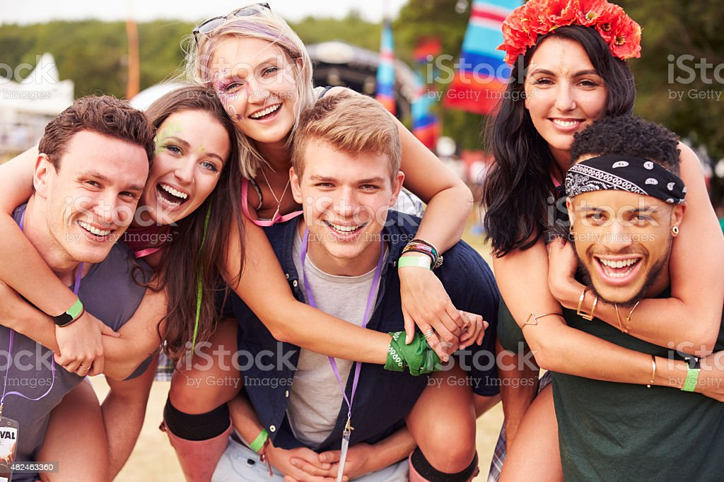 Friends giving piggy backs at a music festival stock photo