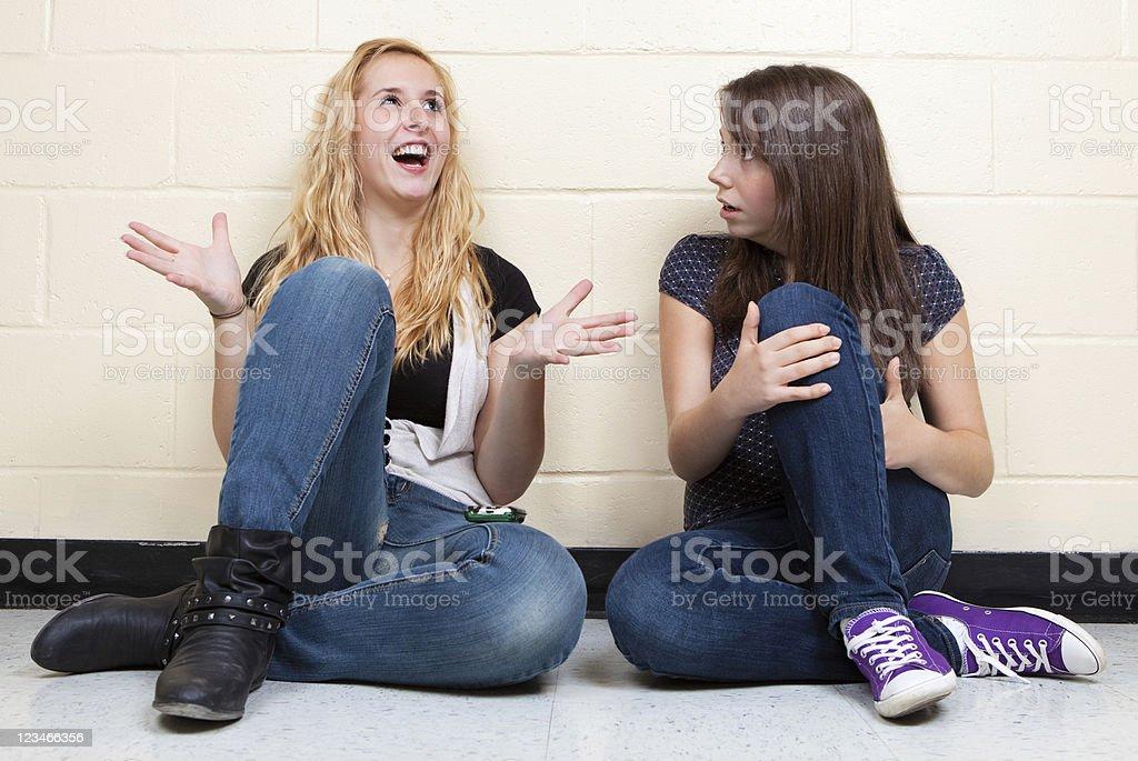 Friends gossiping in school hallway stock photo