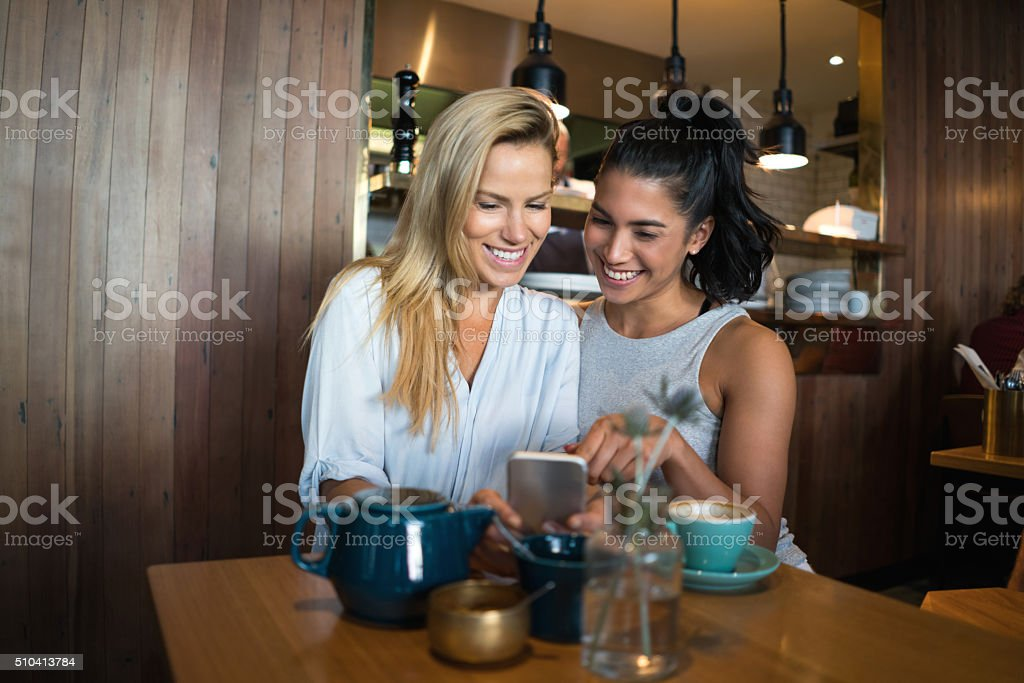 Friends gossiping on a smart phone stock photo