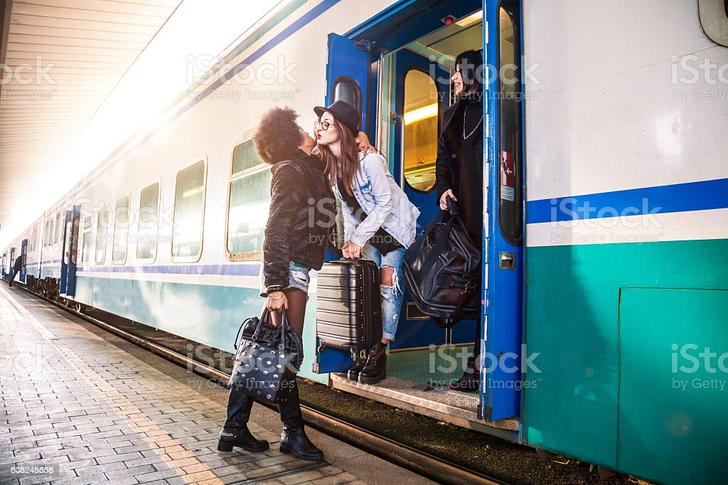 Friends greet at the train station before departure stock photo