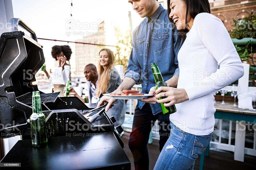 Friends grilling on a rooftop in New York Manhattan stock photo