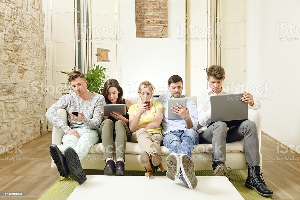 Friends Group, all absorbed with new tecnologies stock photo