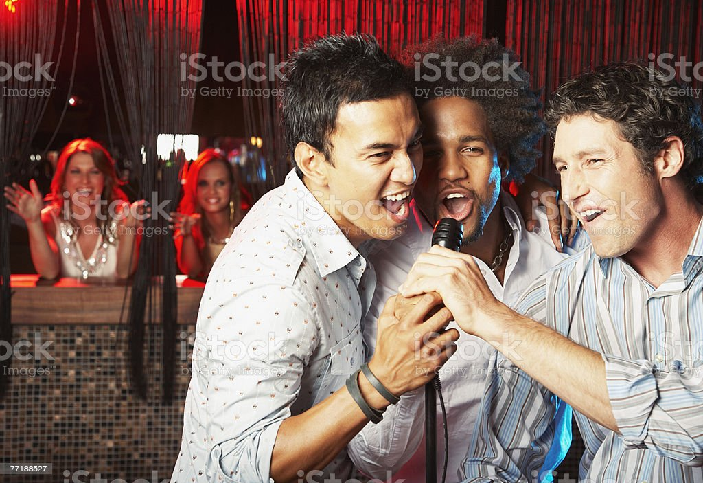 Friends hanging out at a club singing stock photo