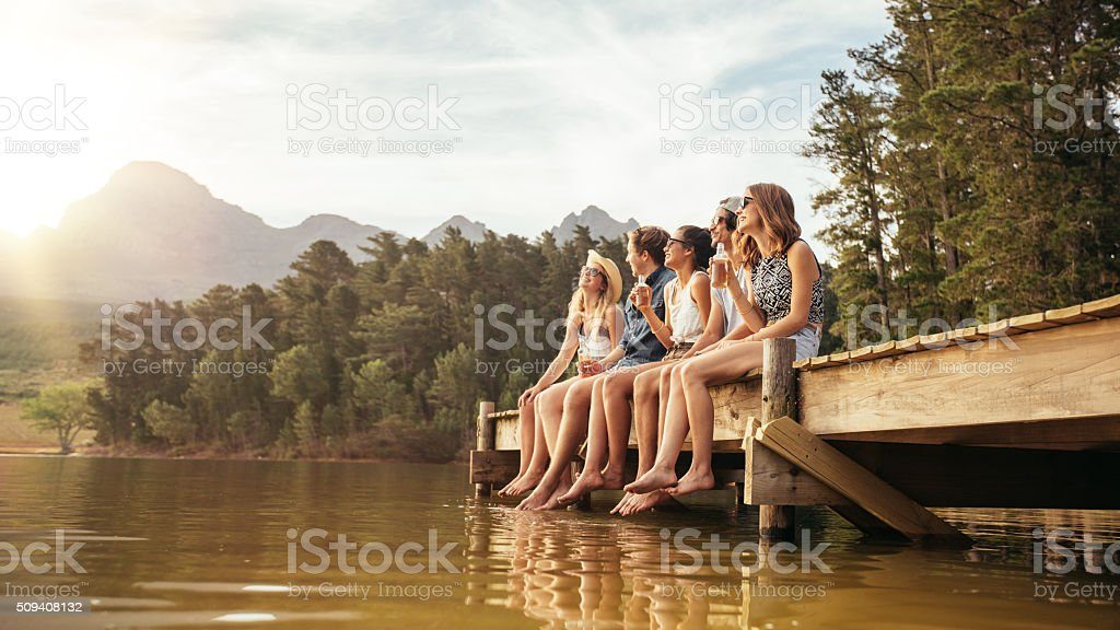 Friends hanging out at the lake stock photo