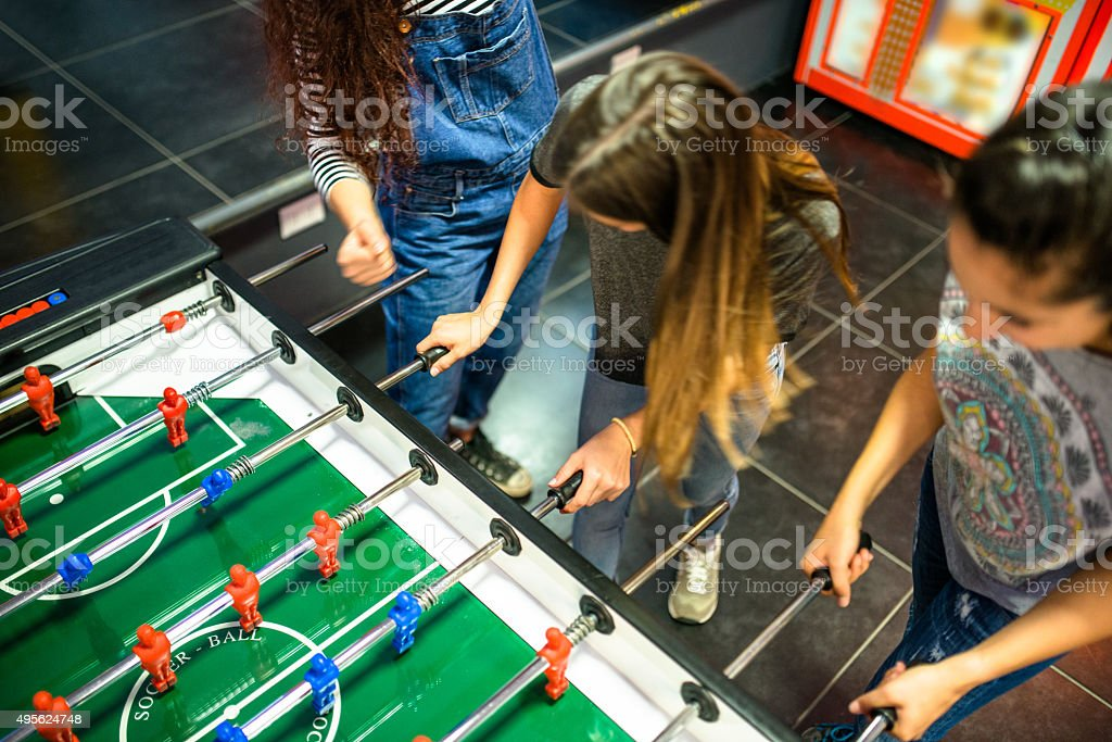 Friends have fun on the game room playing foosball stock photo
