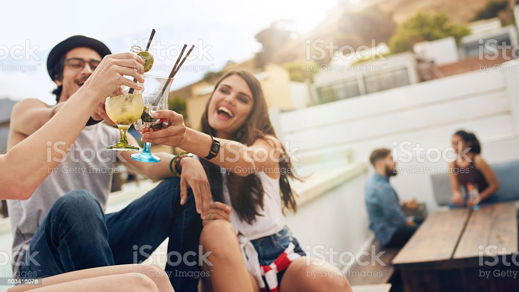 Friends having a cocktail party on roof stock photo