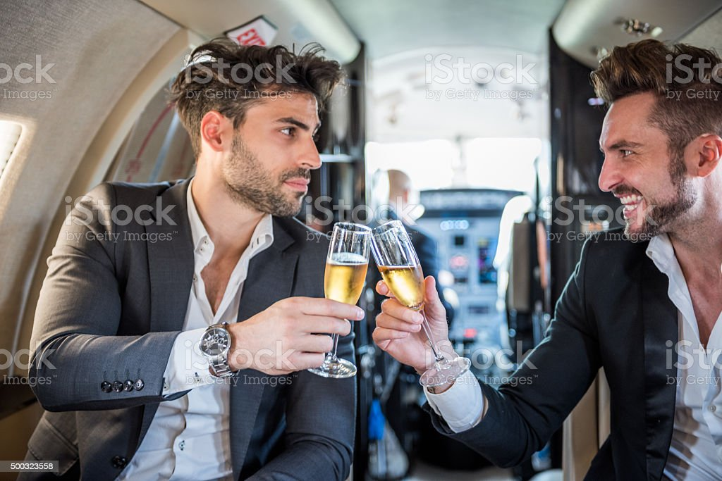 Friends having a toast in private jet airplane stock photo