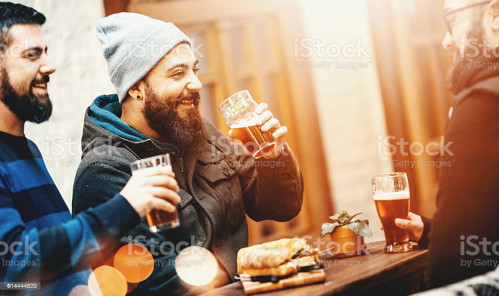 Friends having beers at a pub. stock photo