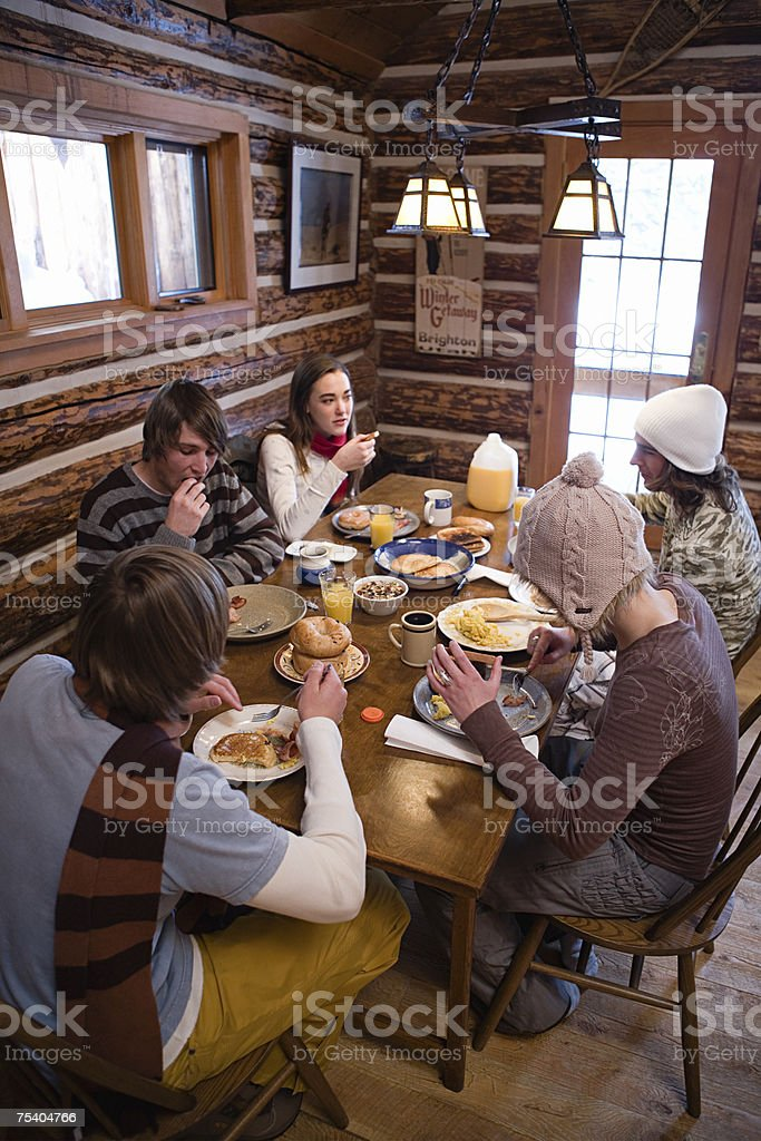 Friends having breakfast in chalet stock photo