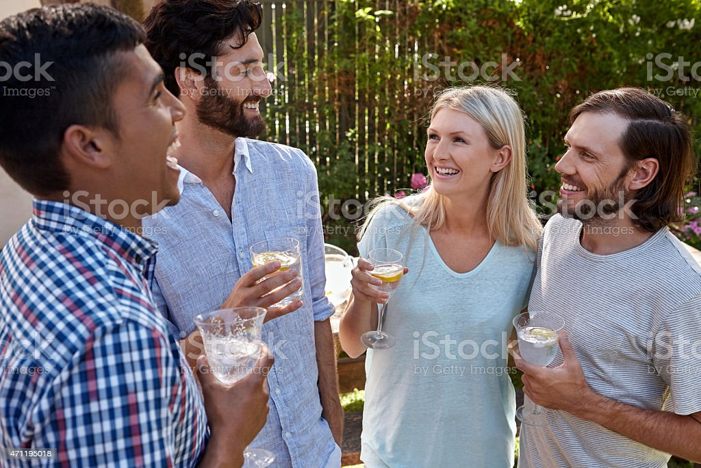 Friends having cocktails in backyard stock photo
