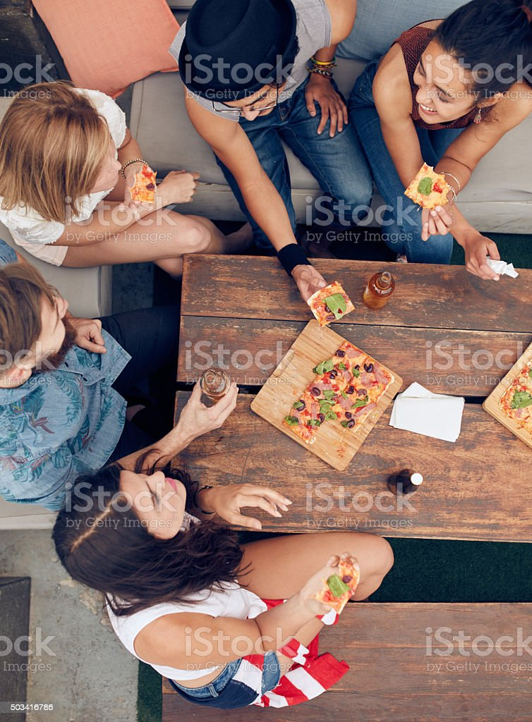 Friends having drinks and pizza at party stock photo
