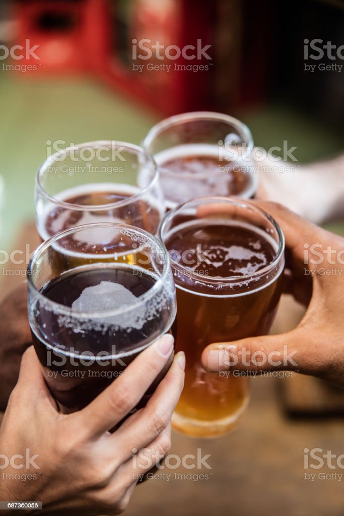 Friends having drinks at the bar and making a toast stock photo