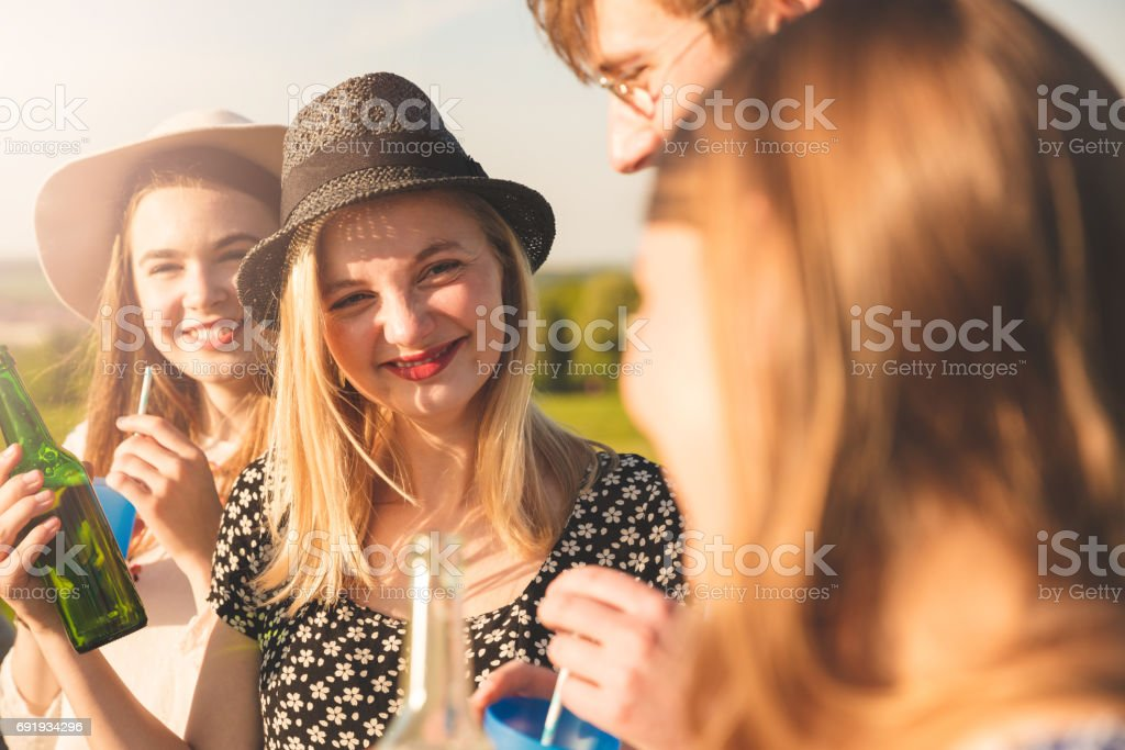 Friends having drinks in picnic on sunny day stock photo