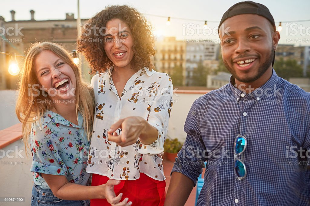 Friends having fun at a rooftop party. stock photo